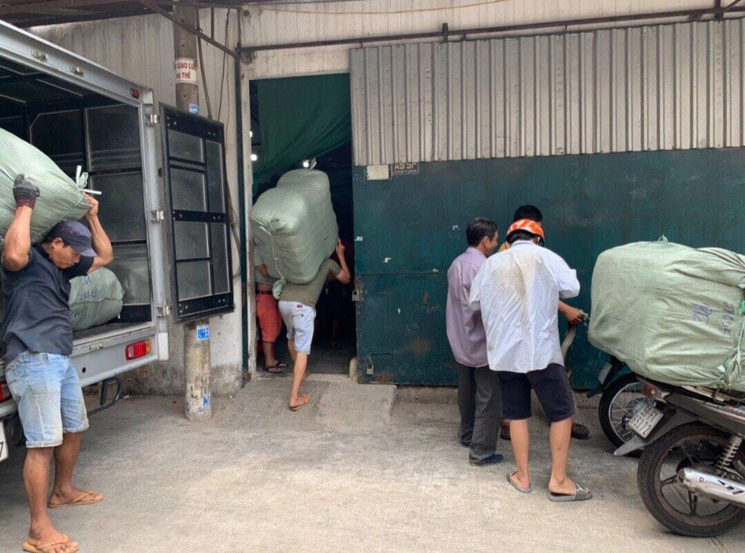 Công nhân bốc vác hàng thùng vào kho tongkhohangsi.com